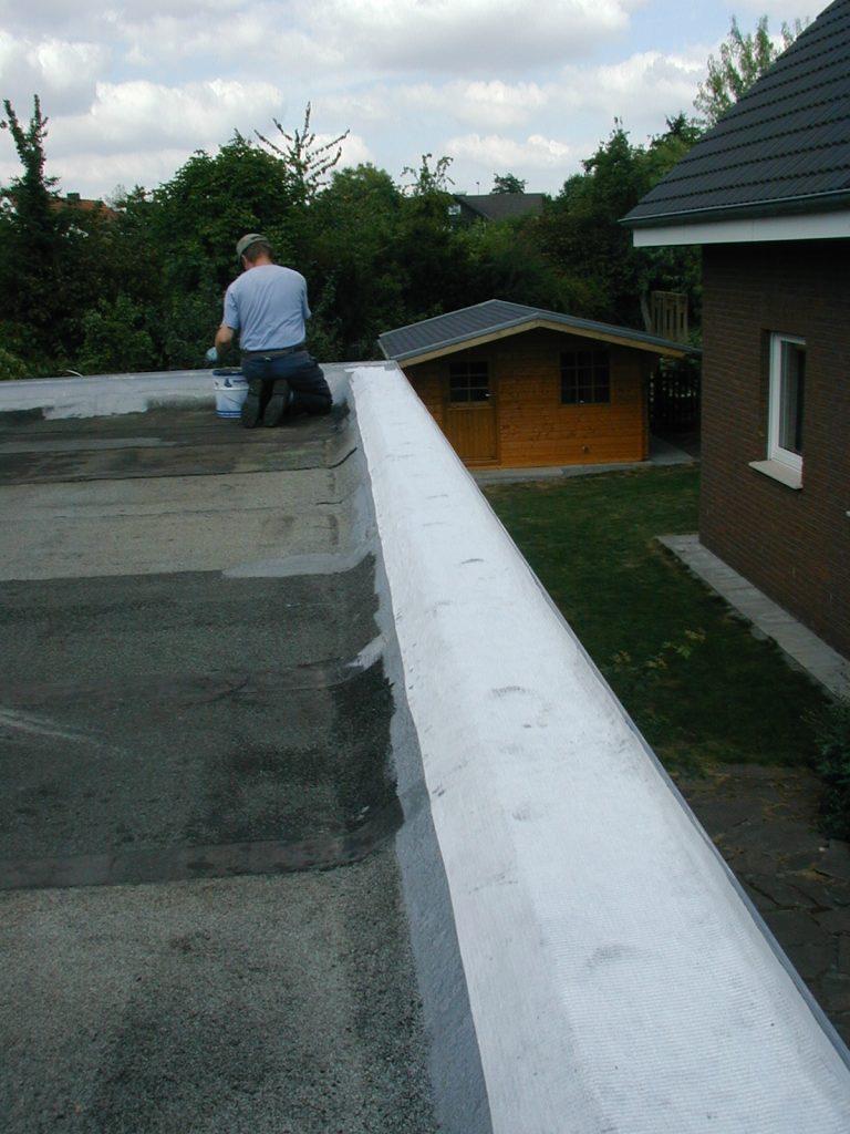 Arbeiter beschichtet Flachdach als Abdichtung
