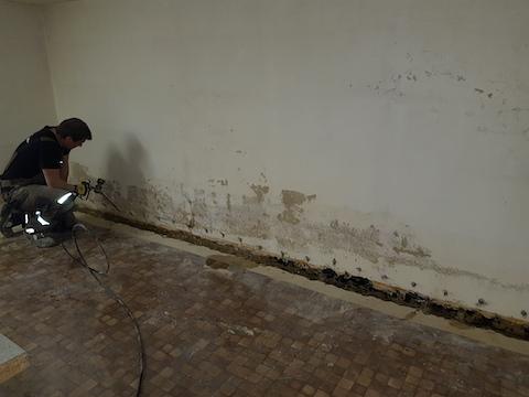 Ein Mitarbeiter erstellt eine Horizontalsperre an der Kellerwand
