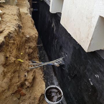 Eine Kellerwand wurde von außen mit Bitumen abgedichtet
